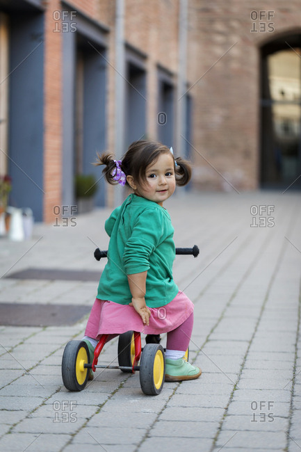 Little girl riding tricycle on patio