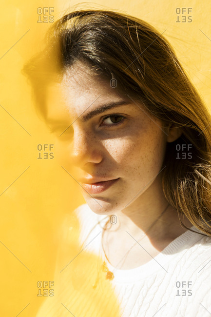 Portrait of a young freckles woman with yellow filter in front of yell