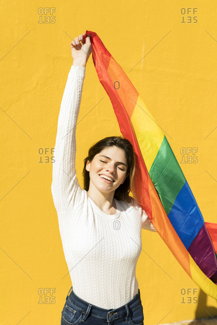 Portrait of a young woman with rainbow flag in front of yellow wall