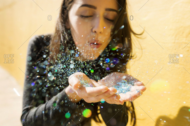 A young woman blowing glitter confetti