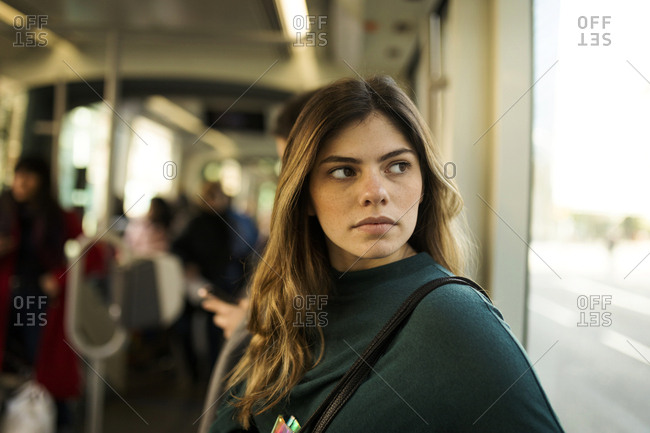 Freckles young woman on train looking out the window