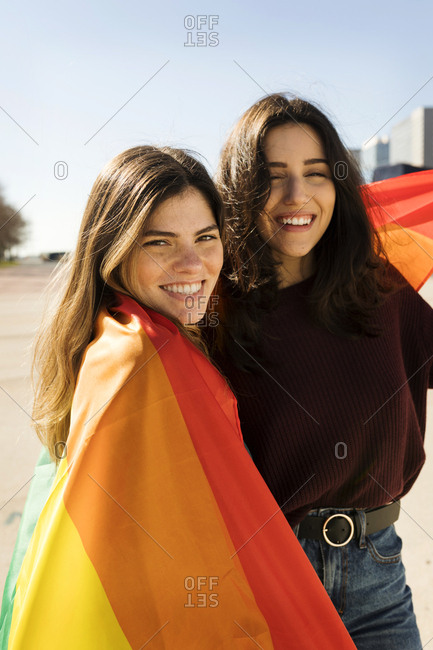 Couple lesbian woman with gay pride flag smiling portrait
