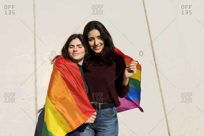 Couple lesbian woman with gay pride flag on the street of Barcelo