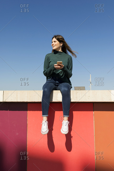 Young woman wearing casual clothes sitting on a colored wall