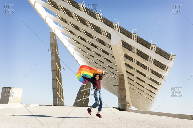 Brunette girl with gay pride flag on a windy day