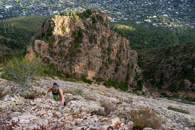 Blonde woman rock climbing above suburban neighborhood