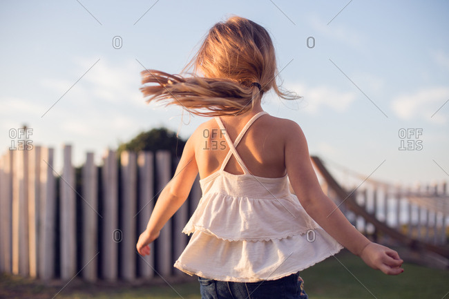 Little girl imagining she's a dancer, spinning and twirling in the sun