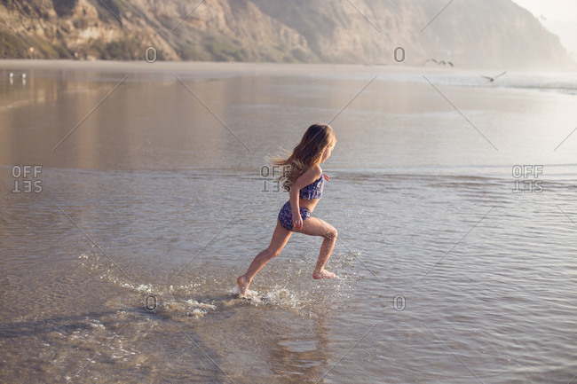 A child runs to the ocean with excitement and wonder in southern Cali