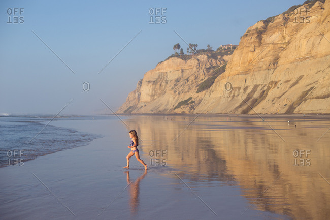 A child runs to independently explore the pacific on a beautiful day.