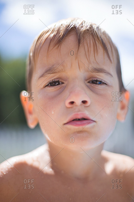 Boy with questioned expression is dripping wet from summer pool.