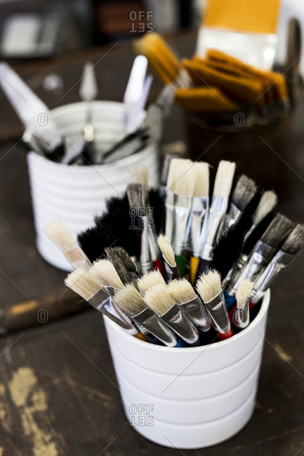 High angle close up of white ceramic pot with selection of paintbrushes in various sizes.