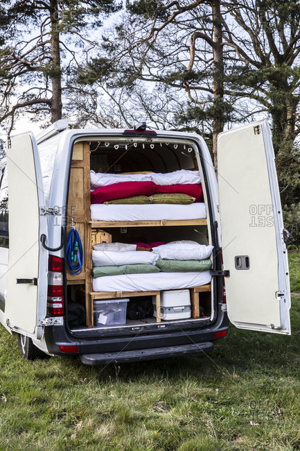 Rear view of camper van parked on a meadow, stacks of mattresses and bedding in back of vehicle.