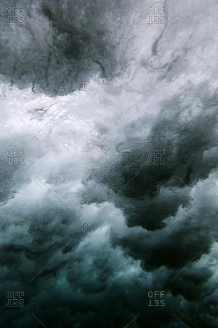 Underwater view of powerful cloudy waves in the ocean