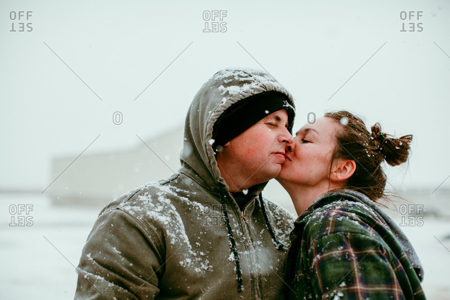 A man and woman kissing in the snow