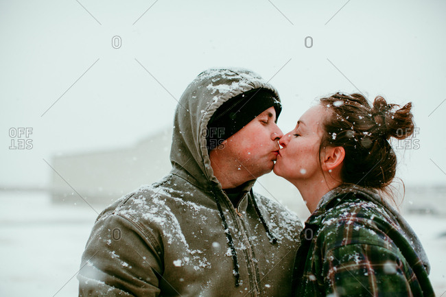 Husband and wife kissing in the snow