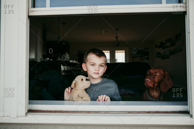 A boy and dog looking out of a window