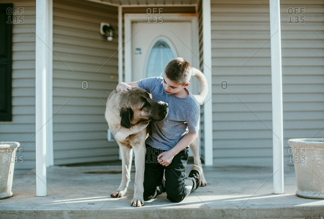 A boy petting a dog on a porch
