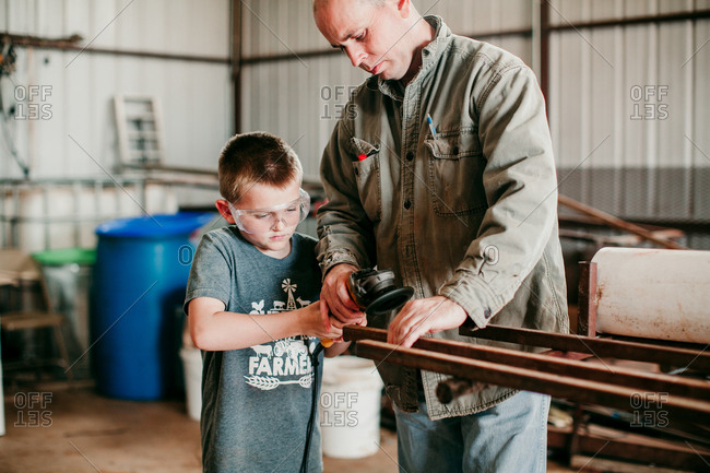 A father teaching a boy how to grind metal