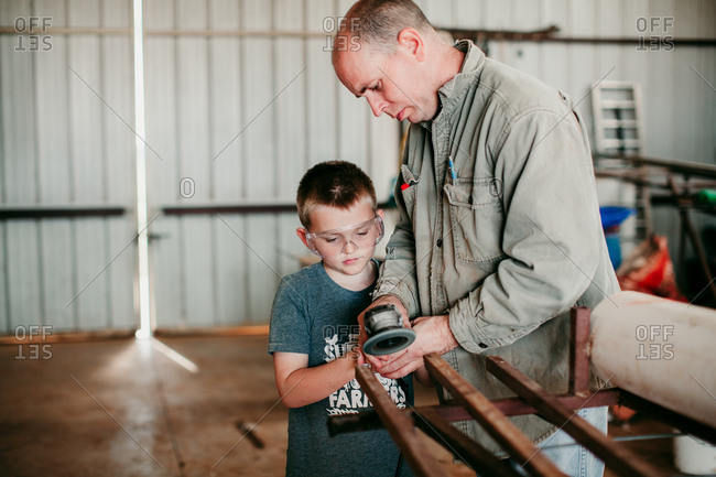 A father helping a boy grind metal