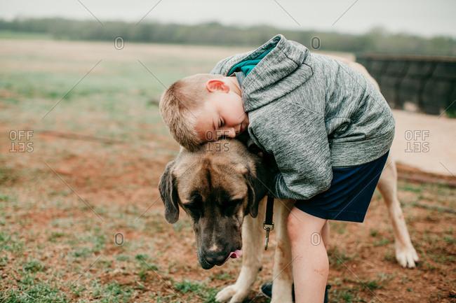 Boy hugging a large dog