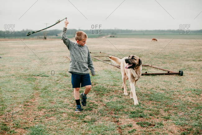 A boy walking a dog while twirling leash in the air