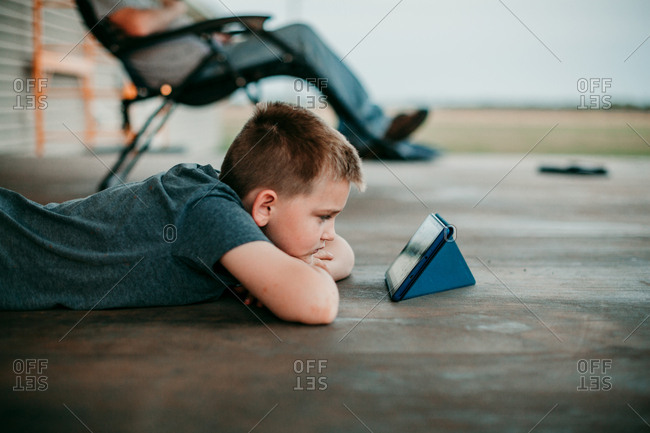 A boy lying on a porch watching videos on a tablet