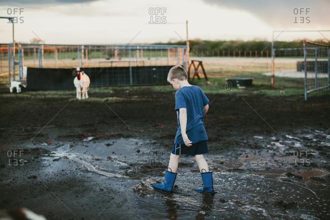 Boy walking in mud on a farm