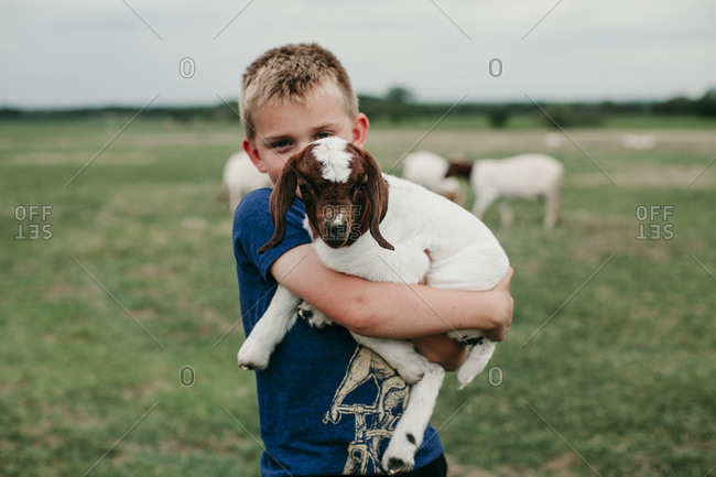 Young boy holding a baby goat
