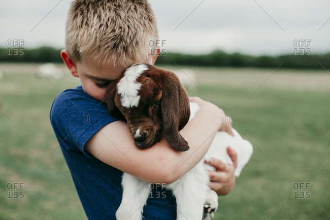 Young boy embracing a baby goat