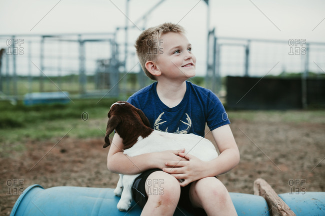 Young boy sitting in pen holding a baby goat