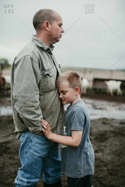 A boy hugging his father outdoors