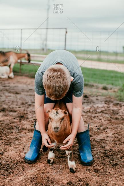 A boy petting a baby goat