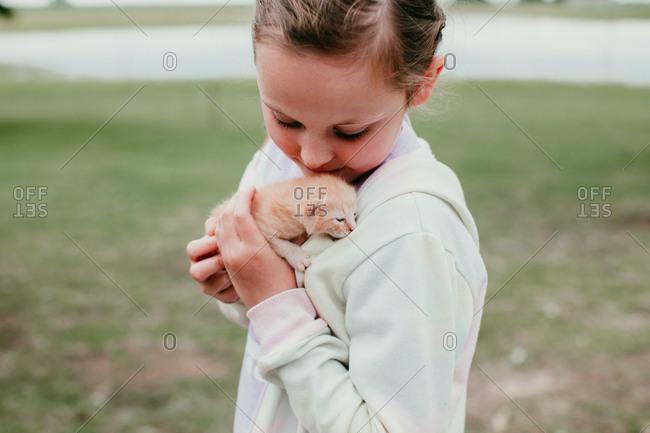 A girl holding a baby kitten