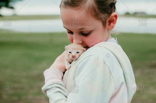 A young girl holding a baby kitten