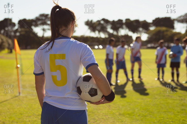 Rear view of Asian female player with ball standing at sports field on a sunny day