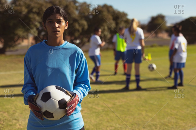 Portrait of Indian female soccer player with ball standing at sports field on a sunny day