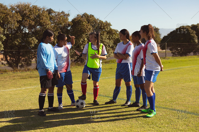 Front view of diverse female soccer players interacting with each other at sports field on a sunny day