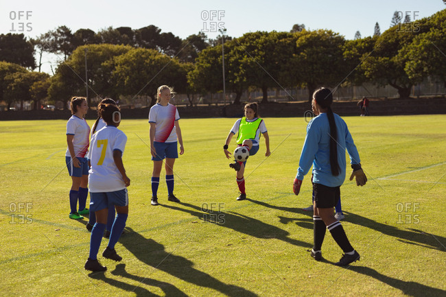 Rear view of diverse female soccer player playing soccer at sports field on a sunny day
