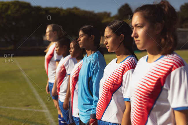 Side view of diverse female soccer player standing in row at the sports field on sunny day