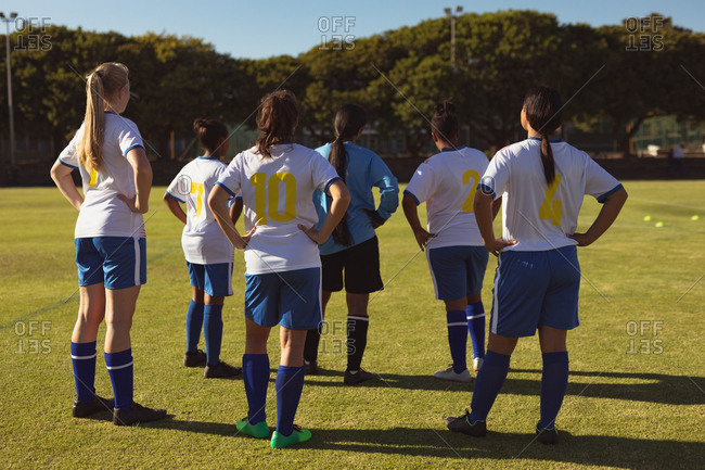 Rear view of diverse female soccer players standing with hands on hip at sports field