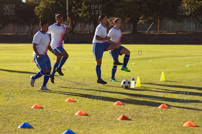 Side view of diverse female soccer players doing warm-up exercise on the field on a sunny day