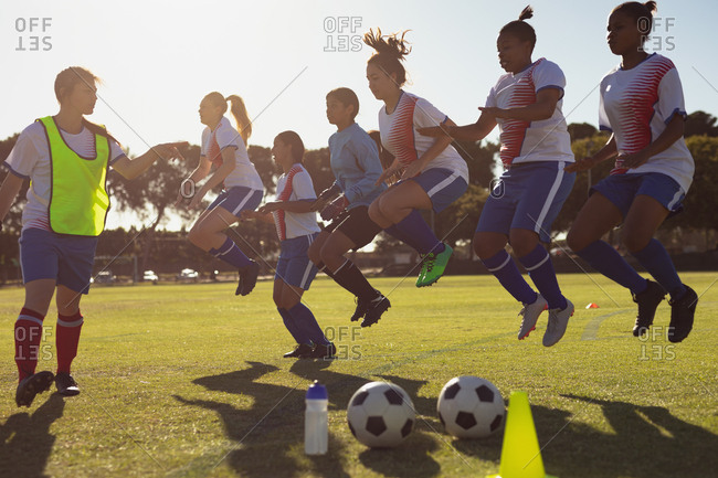 Side view of Caucasian coach helping diverse female soccer players with jumping exercise on the sports field