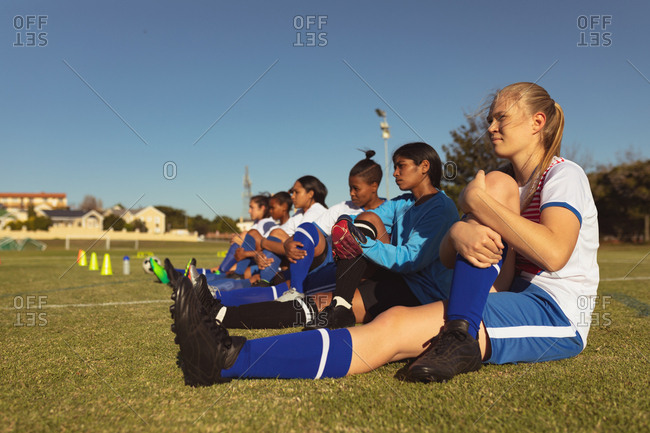Side view of diverse female soccer players doing leg stretch exercise on the field on a sunny day