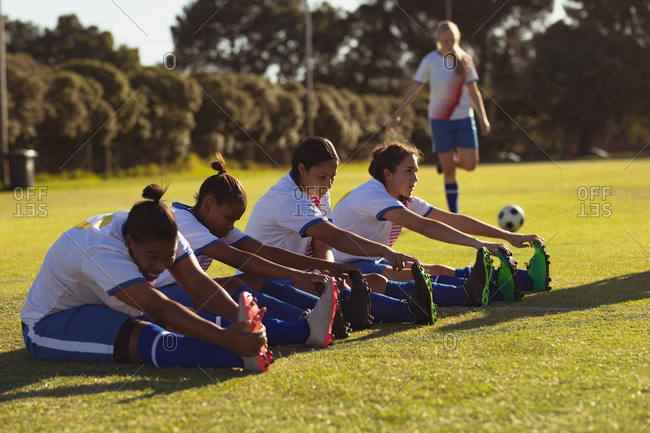 Side view of diverse female soccer players doing stretching exercise on the field on a sunny day