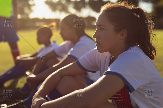Side view of determined diverse female soccer players sitting on the sports field on a sunny day