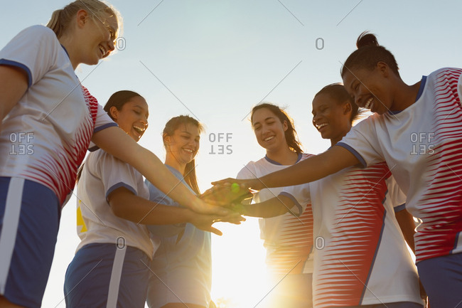 Low angle view of happy diverse female soccer players forming a hand stack on the field on a sunny day