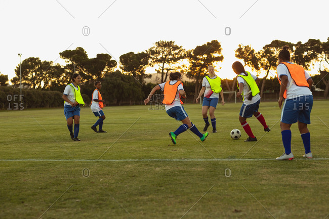 Rear view of diverse female soccer players playing football at sports field at dusk.