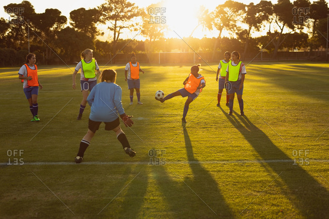 Front view of diverse female soccer players playing at sports field at dusk