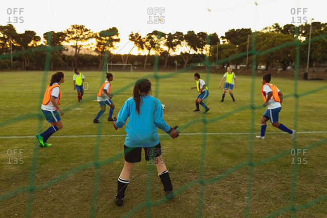 Rear view of determined diverse female soccer players playing at sports field