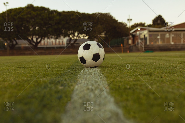 Soccer ball on white line in sports field